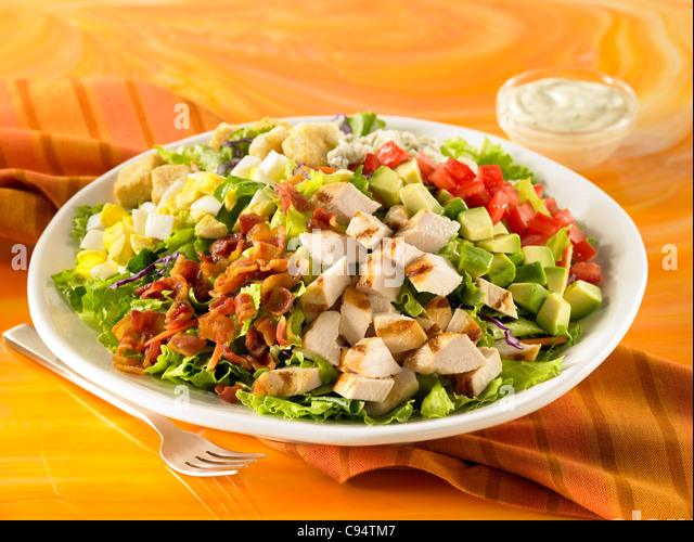 A Cobb salad with grilled chicken, bacon, egg, avocado, cheese and tomato on a bed of lettuce with dressing - Stock Image