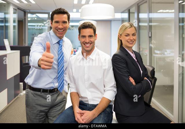 Portrait of joyful business team, man showing thumb up, office background - Stock Image