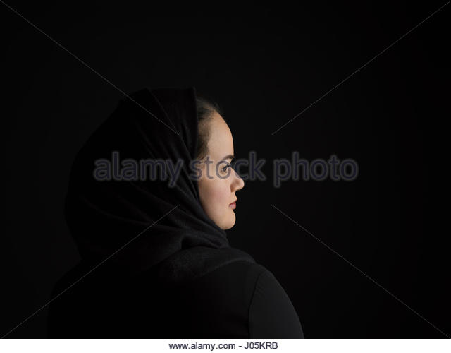 Profile portrait serious Middle Eastern woman wearing black hijab looking away against black background - Stock Image