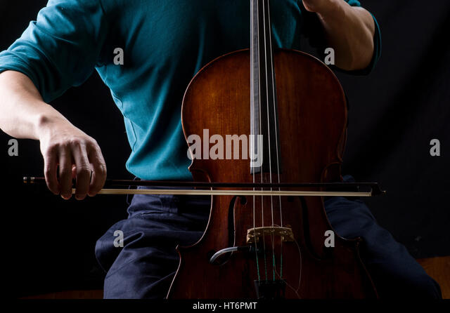 Man in blue shirt playing cello with a bow, his face hidden - Stock Image