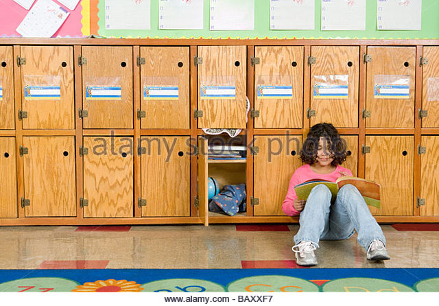 Girl leaning against cubby holes in classroom - Stock Image