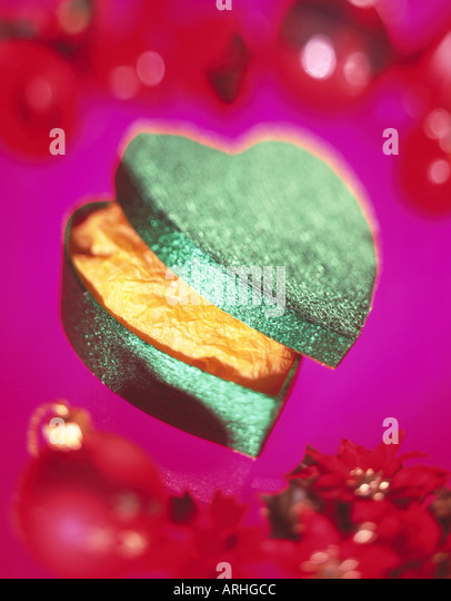 HEART SHAPED VALENTINE GIFT IN WRAPPING PAPER WITH BAUBLES - Stock Image