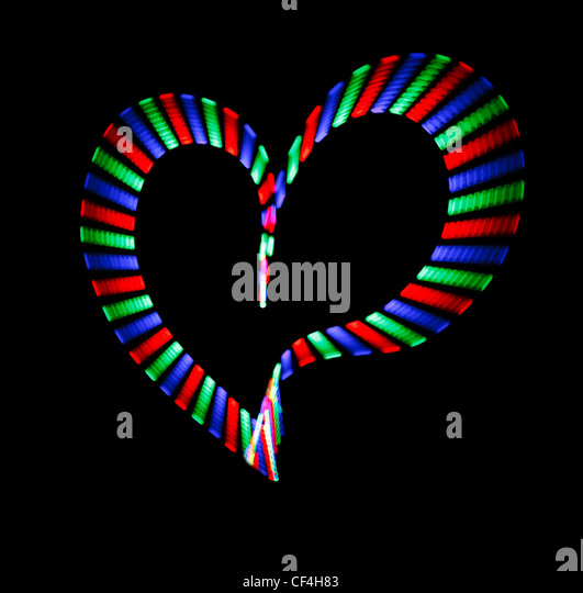 Multi-coloured shone heart on black background. Love symbol. - Stock Image