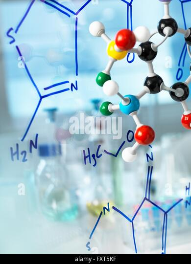 Ball and stick molecular model with formula of new drug written on glass - Stock Image