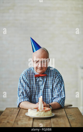 Mature man looking at birthday cake with burning candle on table - Stock Image