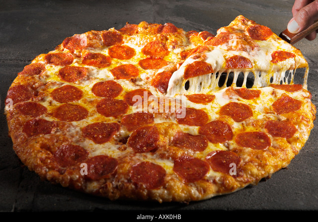 meat pepperoni pizza hand holding slice piece on spatula lifting up warm cheese bred crust on stone table round - Stock Image