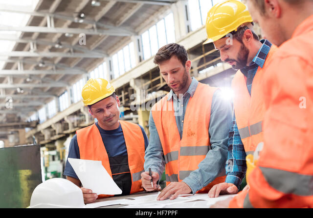 Steel workers and engineers meeting reviewing blueprints in factory - Stock Image