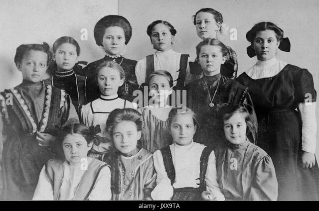 Half length portrait of young girls, African American girl on the left, neutral facial expressions, 1915. - Stock Image
