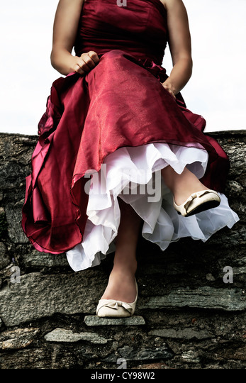 woman sitting on a wall - Stock Image