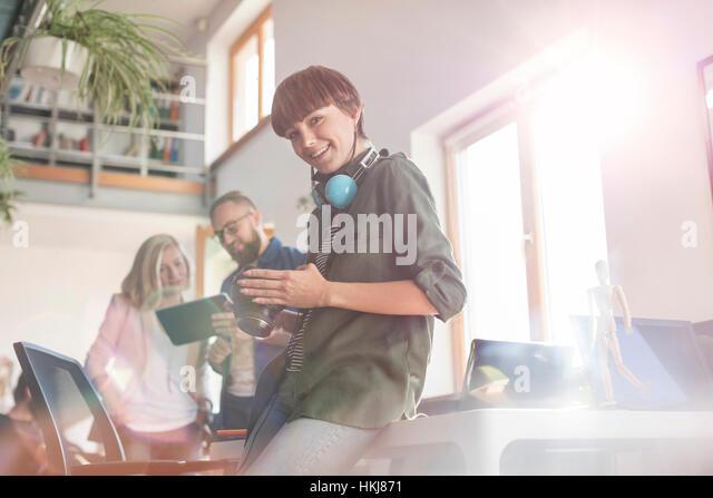 Portrait smiling female photographer design professional with SLR camera in office - Stock-Bilder