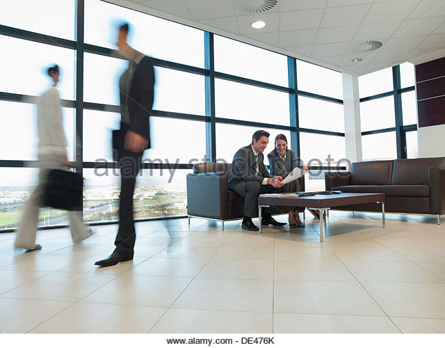 Business people working together in office waiting area - Stock-Bilder