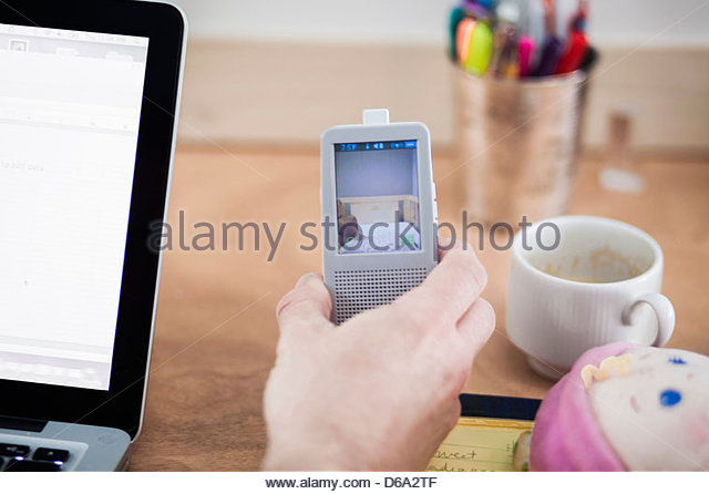 Father using baby video monitor - Stock Image