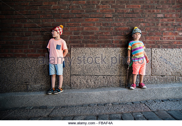 Finland, Helsinki, Boys (4-5) standing against brick wall - Stock-Bilder