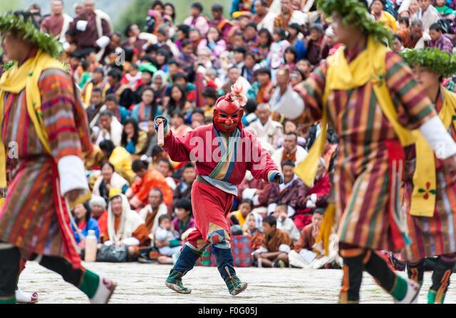 Atsara figure dancing amongst other dancers Paro religious festival Bhutan - Stock-Bilder