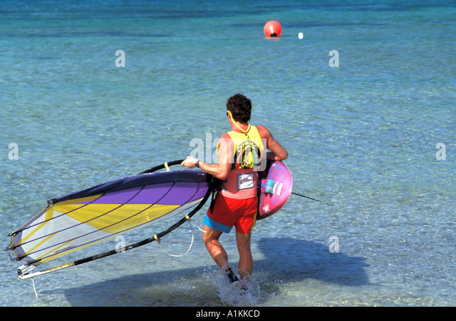 Aruba Wind Surfing at Palm Beach Man Carrying Equipment into Water - Stock Image