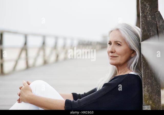 Pensive senior woman relaxing on beach boardwalk - Stock Image