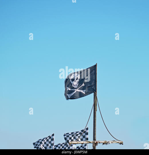 The skull and crossbones of the traditional pirate flag known as the Jolly Roger flying high against a blue sky - Stock Image