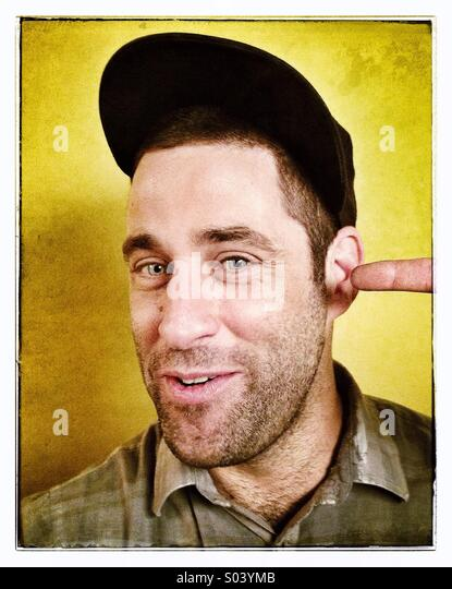 Guy with finger in ear - Stock Image