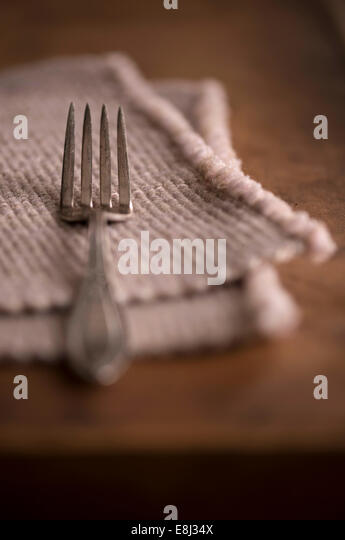 Simple place setting with an antique fork and a vintage placemat on a dark rustic wood table. - Stock-Bilder