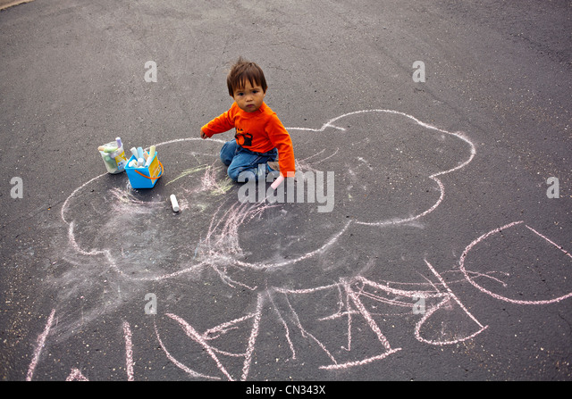 Toddler drawing word dream with chalk - Stock Image