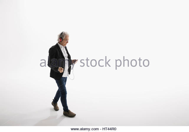 Businessman listening to music with headphones and mp3 player against white background - Stock-Bilder