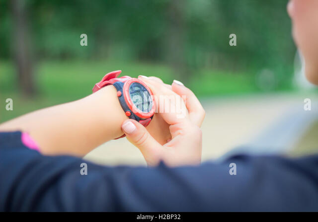 Young fitness girl checks stopwatch tracker on her wrist during running outdoor - Stock Image