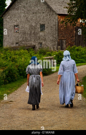 Girls dressed in old fashioned clothingat King's Landing, New Brunswick, Canada - Stock Image
