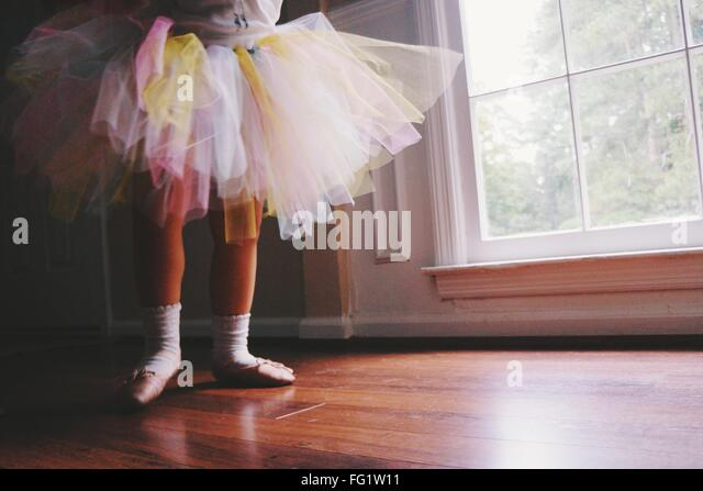 Low Section Of Ballerina Standing On Hardwood Floor At Home - Stock Image