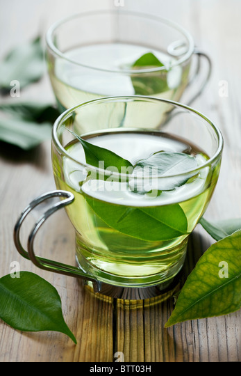 closeup of fresh green tea, focus on the tea leaves in the water - Stock Image