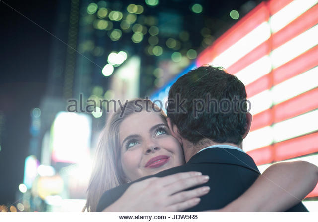 Neon american flag and young couple hugging, New York City, USA - Stock-Bilder