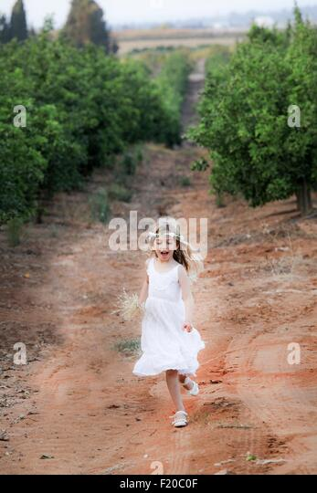 Young girl running in orchard, Israel - Stock Image