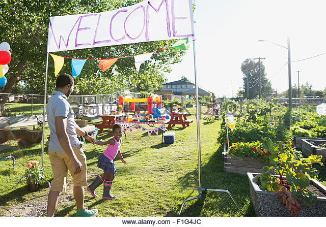 Father and daughter arriving under Welcome sign park - Stock Image