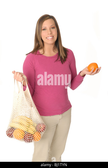 Attractive young woman with reusable grocery shopping bag filled with fresh fruit. - Stock-Bilder