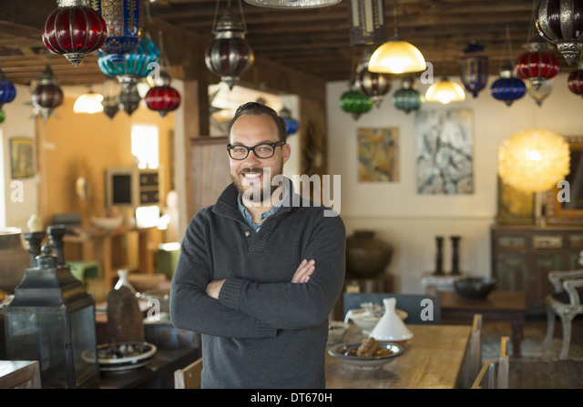 A man standing in a shop full of antique and decorative objects. Antique shop displays. Lighting, glass shades and - Stock Image