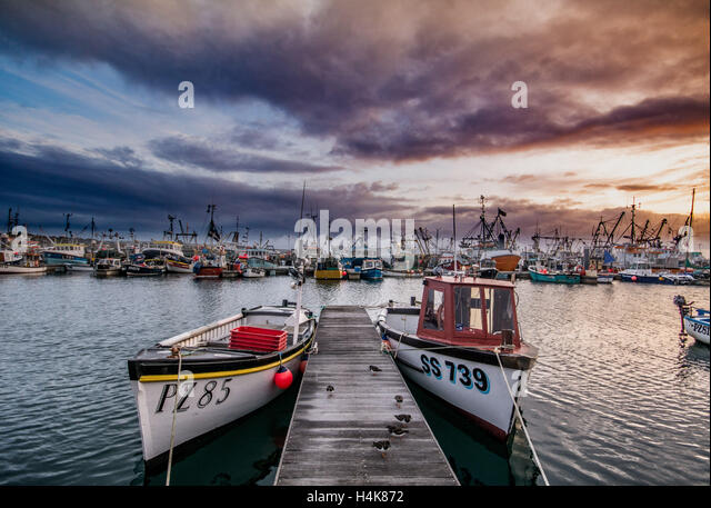 Newlyn, Cornwall, UK. 18th October 2016. UK Weather. The sun rises behind the clouds over Newlyn harbour. The night - Stock Image