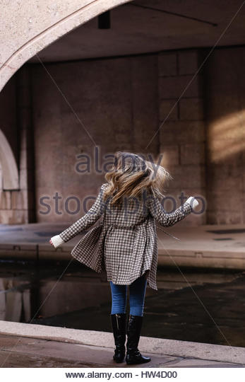 Rear view of a young woman with long hair swingin - Stock Image