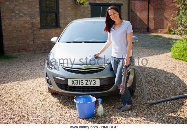 Portrait happy woman washing and vacuuming car in sunny summer driveway - Stock-Bilder