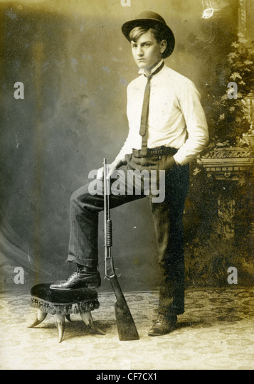 Boy standing wearing suit and bowler hat during late 1800s or early 1900s 22 caliber pump action rifle guns gun - Stock Image