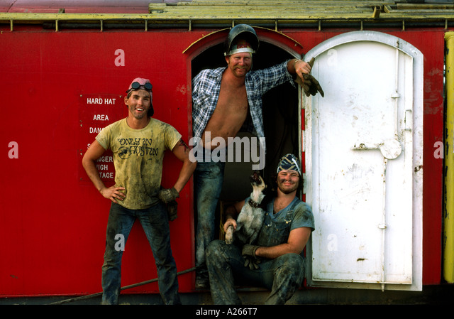 Three young dirty rough necks pose against a red wall and white door with their cute mutt on rig in South Texas. - Stock-Bilder