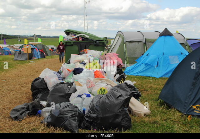 Rubbish overflows from a bin by festival goers' tents  on the final day of  the Y Not festival, Pikehall, Derbyshire - Stock Image