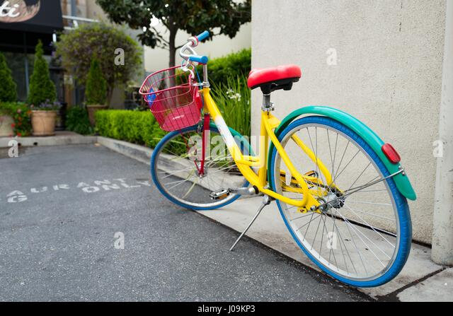 Colorful Google Bike parked near a wall in a shopping center near the Googleplex, the Silicon Valley headquarters - Stock Image