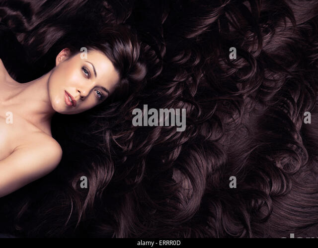 Beauty portrait of woman surrounded by long brown hair. Hair extension concept. - Stock-Bilder