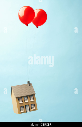 House floating away with two balloons - Stock-Bilder
