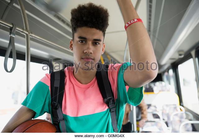 Portrait serious young man with basketball riding bus - Stock Image
