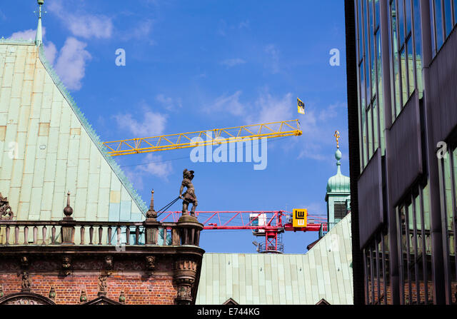 Modern construction cranes behind the Rathaus Bremen, with reflections from the State Parliament building. - Stock Image