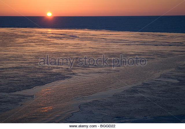 Alaska, Bering Sea. Polyna freezing up in late winter. Sunset. - Stock Image
