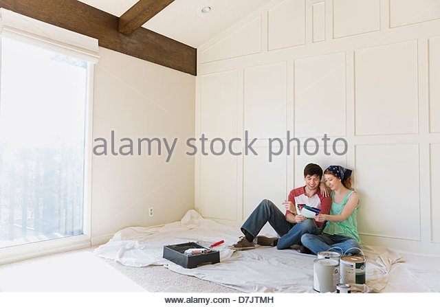 Young couple choosing paint colors at home - Stock Image