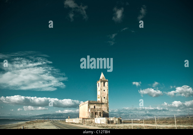 Abandoned building on coastal road under blue sky - Stock Image