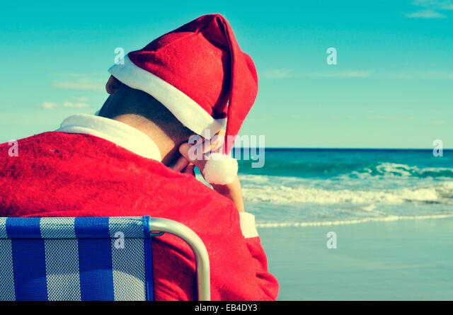 santa claus taking a nap in a beach chair on the beach - Stock Image