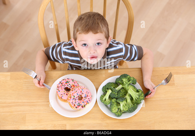 Young boy with plates of broccoli and doughnuts - Stock-Bilder